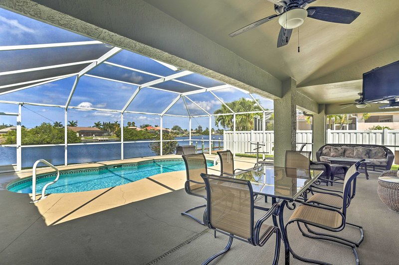 Enjoy this covered patio and pool when you book this Cape Coral vacation rental.