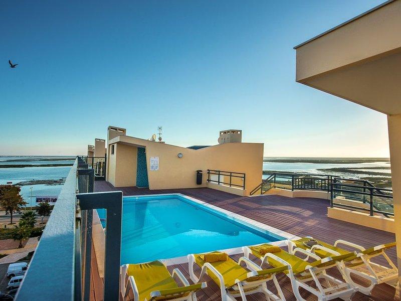 Piscina en la azotea con terraza y sillas.