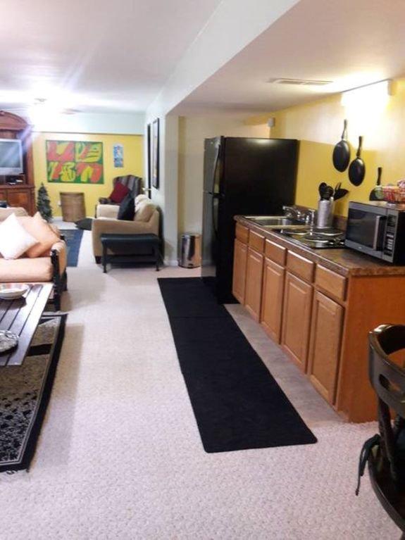Área de cocina con nevera, cuatro quemadores de cocina eléctrica, ollas, sartenes, cafetera y tostadora.