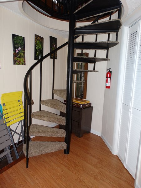 Circular staircase leading downstairs. Porch chairs on the left for seating outside.
