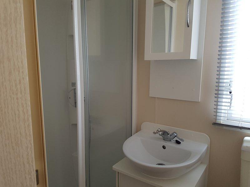 Salle de bain familiale avec douche. Les portes menant à la chambre principale et au hall.