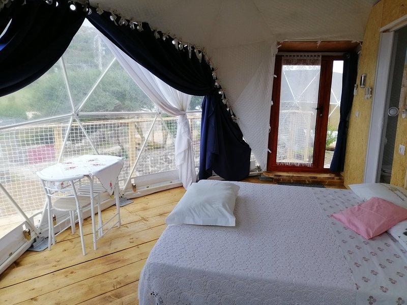 El amplio dormitorio principal con ventana de cristal con vistas al mar.