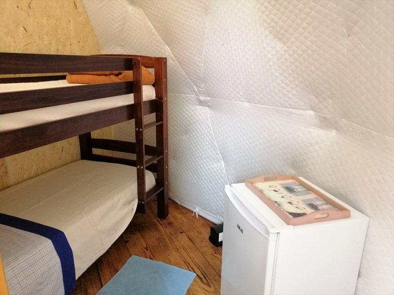 El dormitorio con la litera y la nevera.