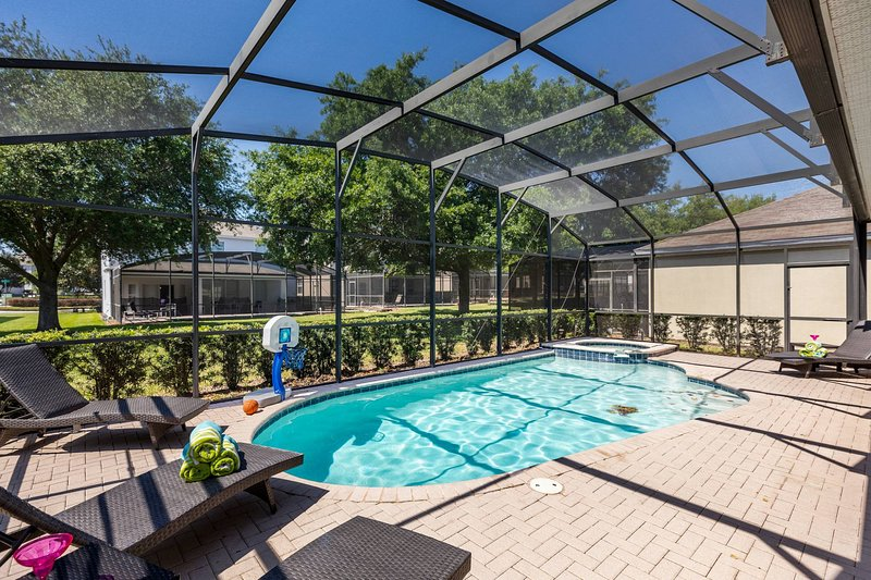 The covered lanai, lounge chairs & basketball hoop, salt water pool & spa