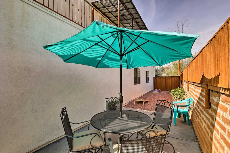 Sip drinks under the shade of the umbrella at this Tucson vacation rental house.
