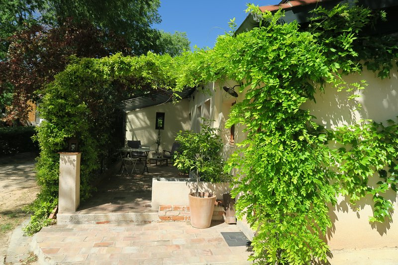 The entrance to the bastide's outbuilding and its private terrace, with fragrant jasmine and wisteria