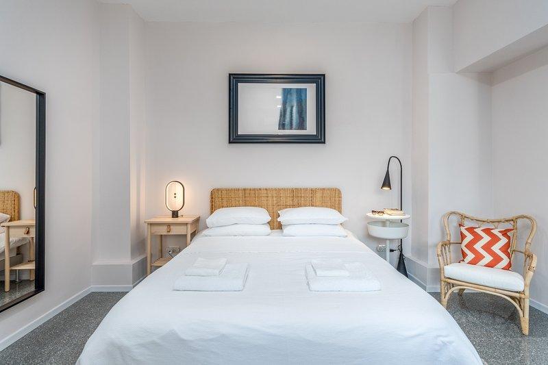 Una cama queen size con sábanas limpias, toallas y batas de baño.