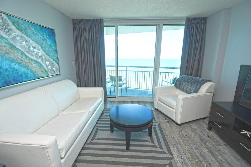 Sala de estar con balcón con vista al mar