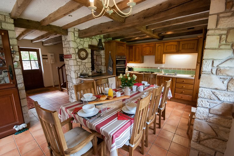 Kitchen area with large table and chairs that comfortably seats 8 guests