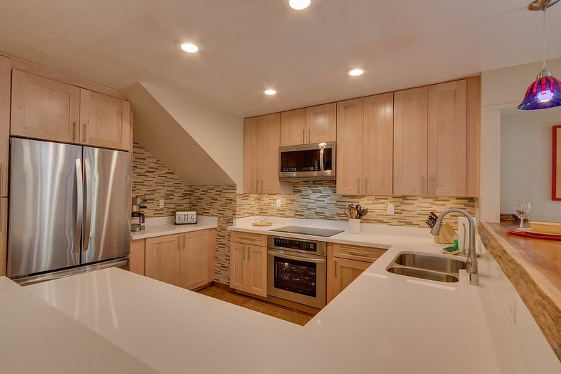 Kitchen with stainless steel appliances, wooden cabinets, and white counters