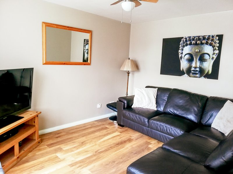 Living room which includes a large 46 inch Sony TV a large leather corner sofa and a ceiling fan