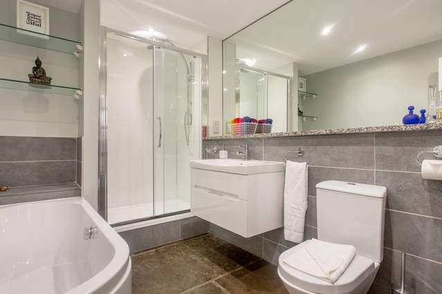 Bathroom with rainwater shower, large bath and underfloor heating. Heated mirror.