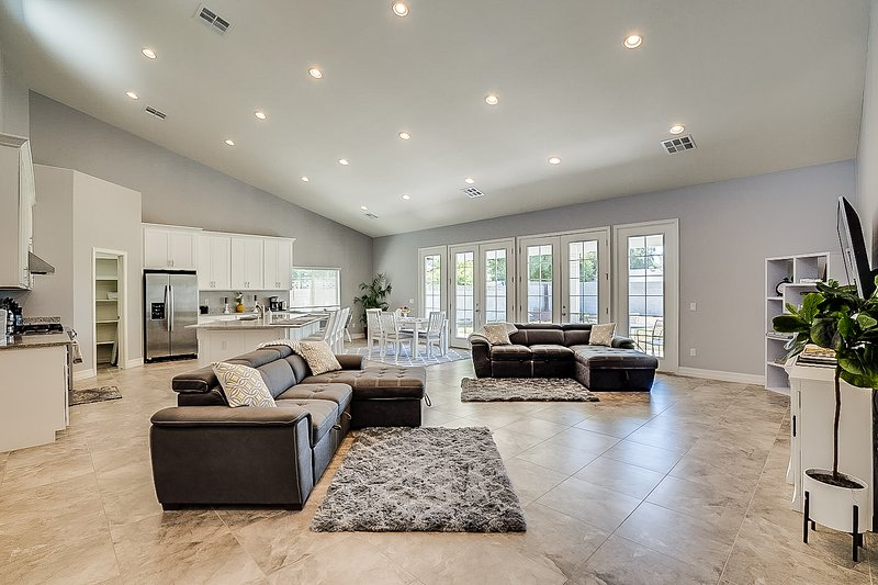 The gorgeous living area features tasteful decor, french doors, and comfortable seating.