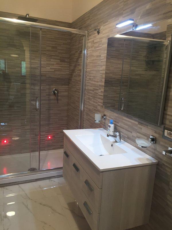 Baño con amplia cabina de ducha con luces led.