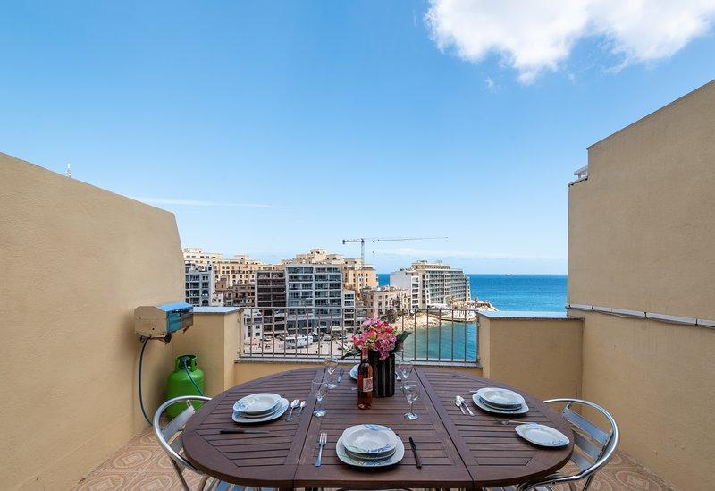 Terraza frontal con vistas al mar con barbacoa y muebles de exterior.