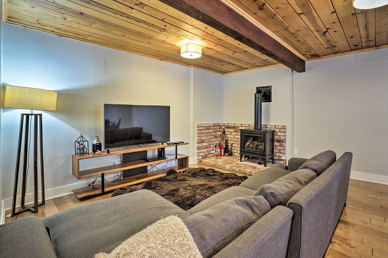 Nedre vardagsrummet har en plattskärms-TV och en öppen spis.