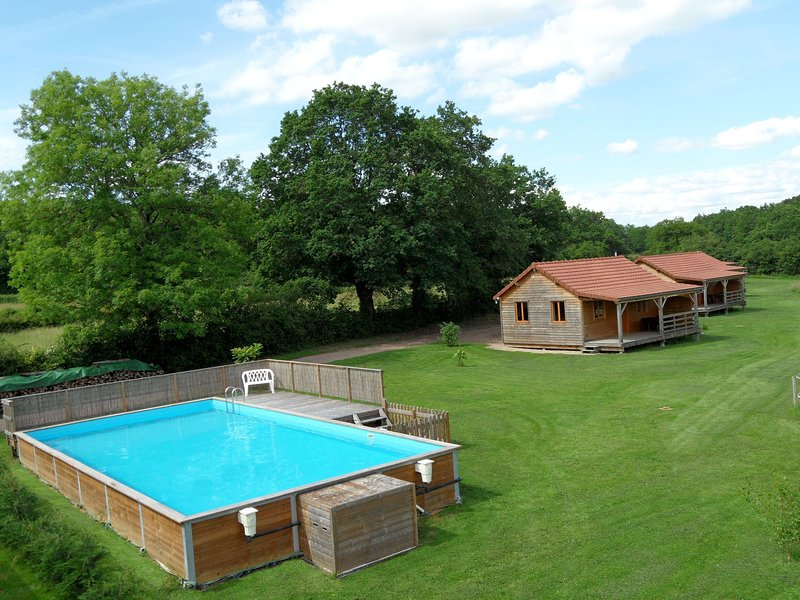 The outdoor swimming pool and the 4 chalets on our property.