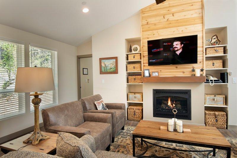 Salon avec foyer au gaz et télévision à écran plat