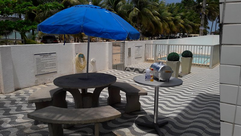 Common area in front of the flat, with small table and private barbecue accessories.