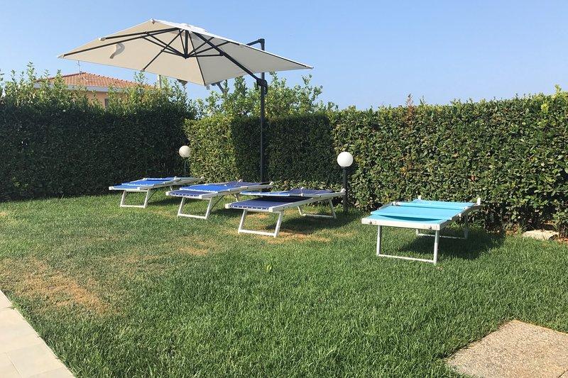 Jardín con sombrilla y tumbonas.