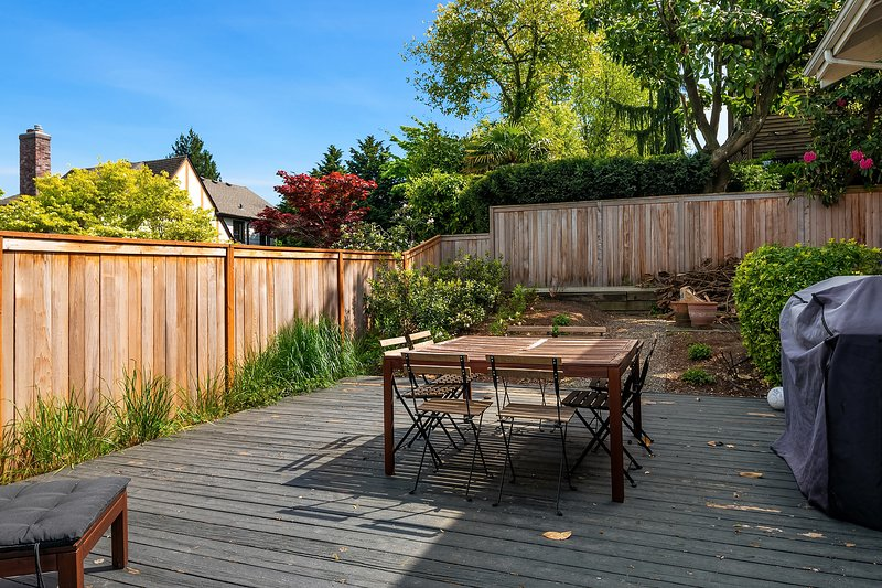 The backyard of the home features a BBQ grill and table.