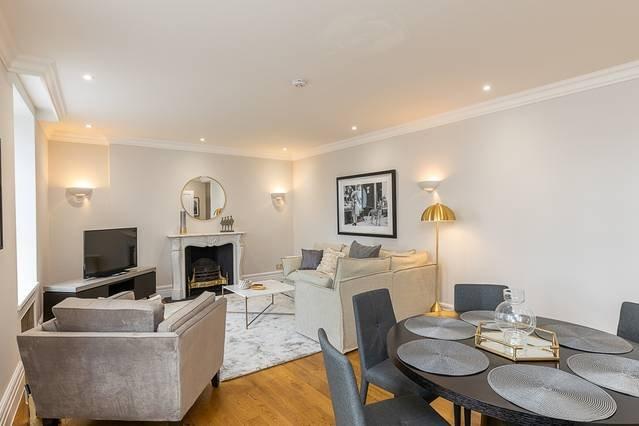 Vardagsrummet är möblerat med en soffa, en fåtölj, ett soffbord och en platt-TV.