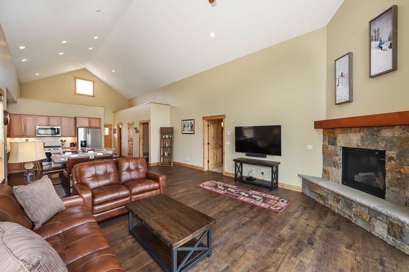Plan d'étage ouvert avec des plafonds voûtés dans le salon, une cheminée à gaz et des sièges confortables