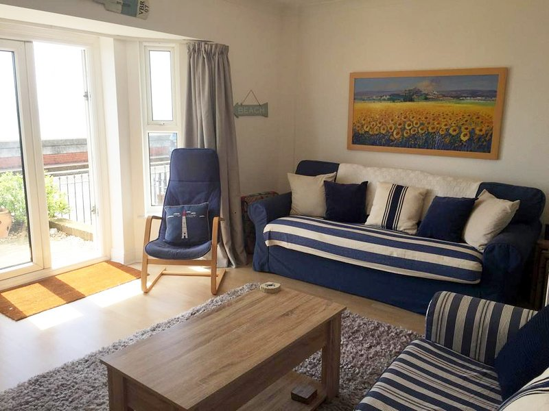Sitting room with patio doors leading to the seafront garden. Seats six comfortably.