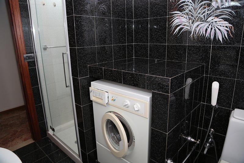 Casa de banho com chuveiro, WC, máquina de lavar roupa