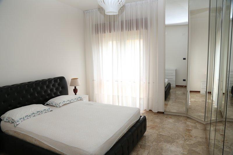Quarto com cama de casal e armário com espelho de 7 portas