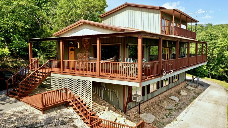 3 story waterfront house with lots of large windows, a wrap around deck and 3rd floor balcony.