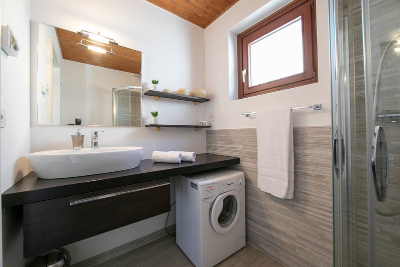 Bathroom with washing machine and shower