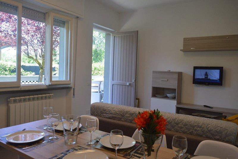 Vista de la soleada sala de estar con TV de pantalla plana y área de comedor