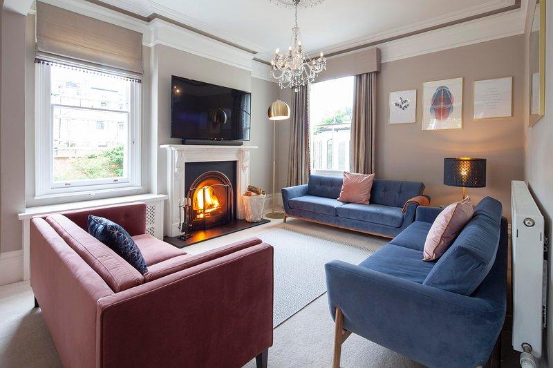 """Sala de estar con chimenea y televisión y sonido con una experiencia cinematográfica de 65 """". Cómodos asientos 10+"""