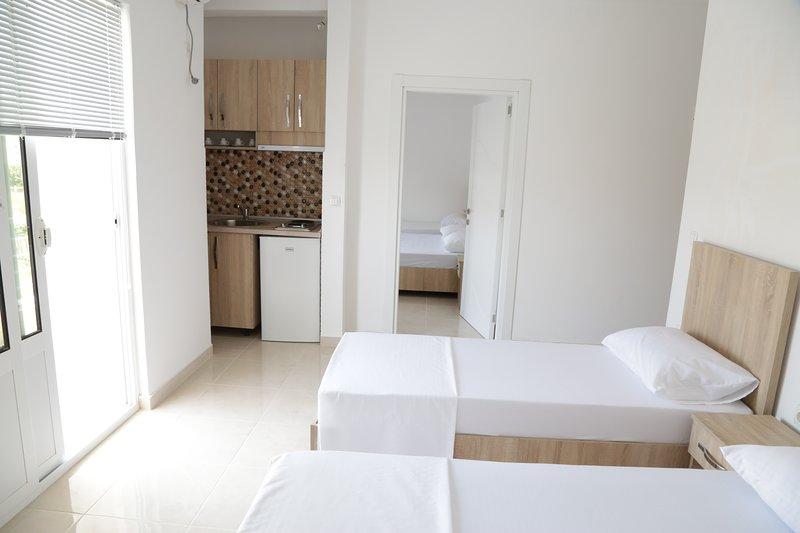 Camera da letto numero uno con cucina e balcone dotati di un letto matrimoniale e uno singolo