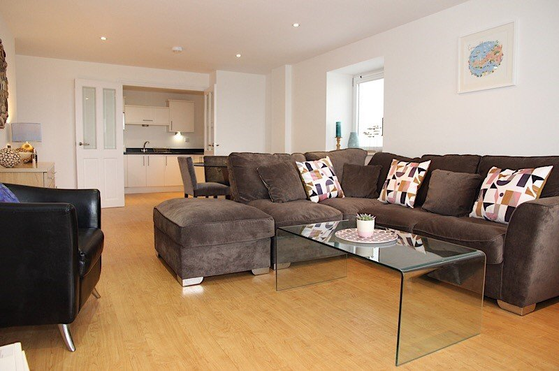 Open plan lounge, kitchen and dining area with patio doors to outside patio area, sea glimpses.