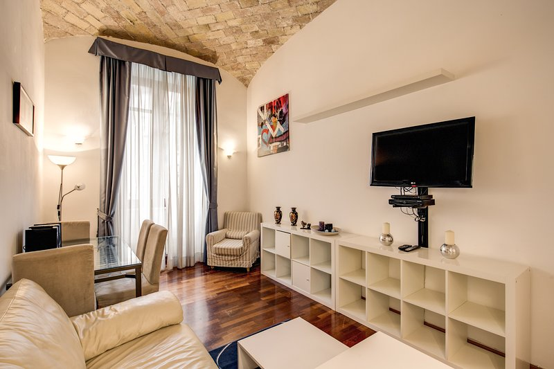 Living room with double bed sofa, TV, dinner table, chairs and AC