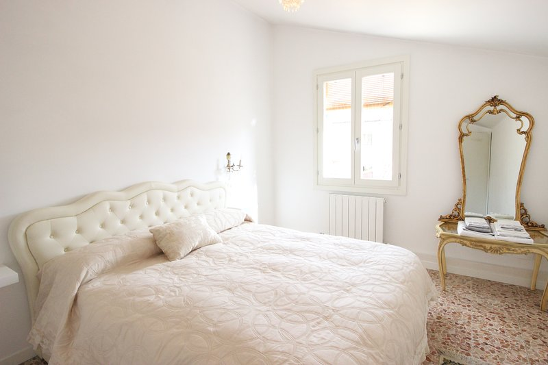 bright room with double bed, mirror, wardrobe,rooftop view