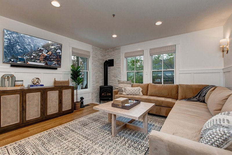 Main Level Living Room with a Large Sectional Sofa, Gas Pot Belly Stove, 55' Smart TV with Xfinity Cable