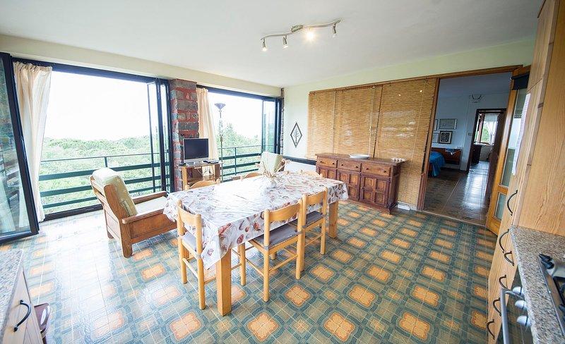 Cucina all'interno di una veranda con vista sul mare e sui pini