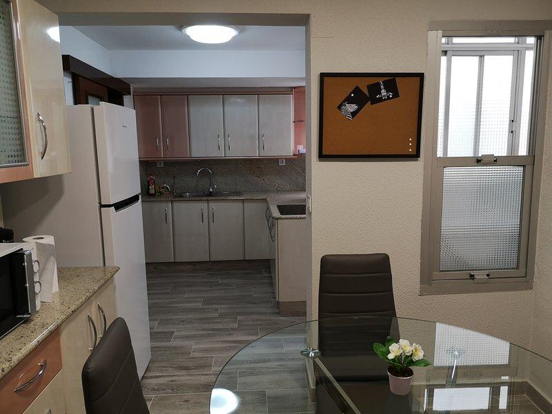 A cozinha tem uma área de jantar, microondas, cafeteira e geladeira
