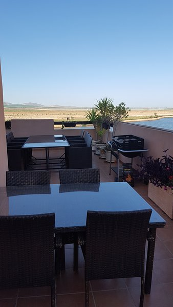 Two patio tables (seating 8 and 4 respectively) as viewed on our 15 yard long side terrace.