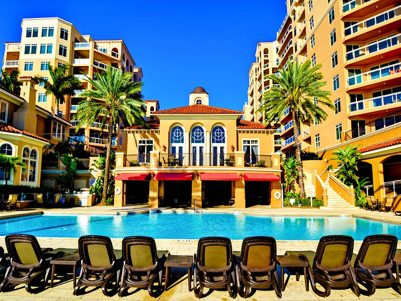 Florida-Beach-Rentals-Belle-Harbour-pool-building-loungers-table
