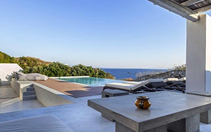 Área lounge junto a la piscina con vista al mar.