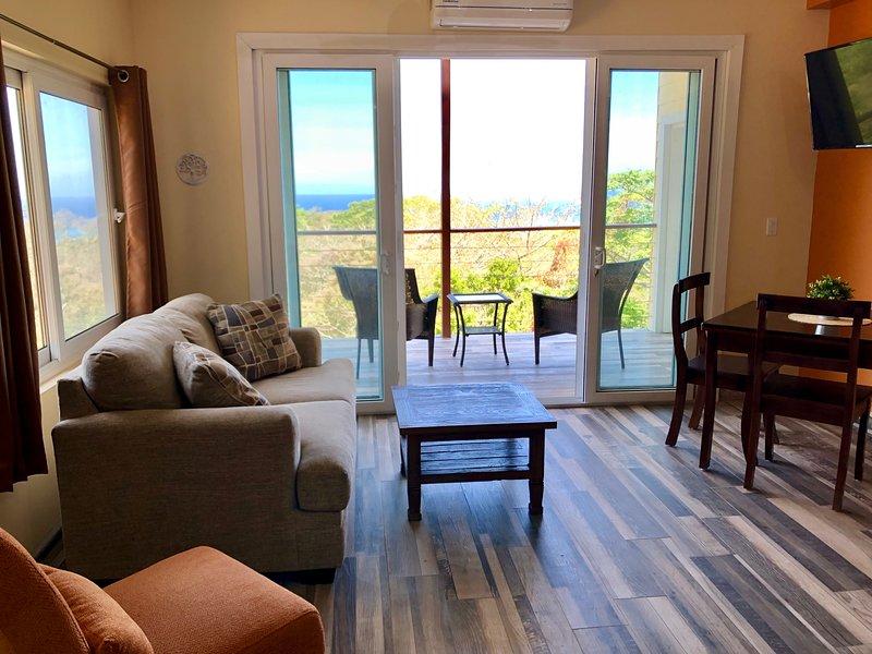 La sala de estar de concepto abierto fluye hacia su terraza privada de 15 pies, con vista a la selva y al mar