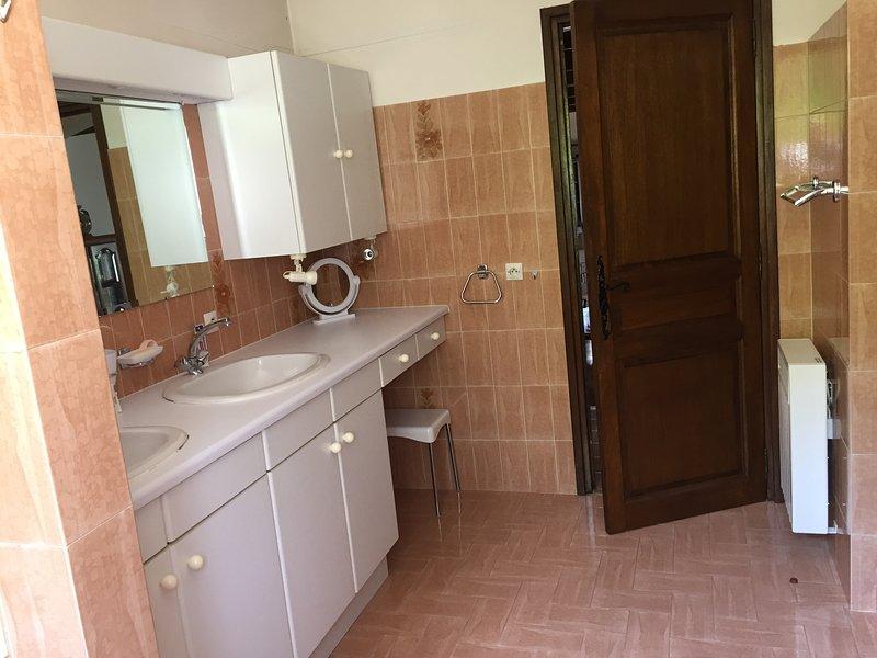 Salle de bain avec toilette, douche et bain.