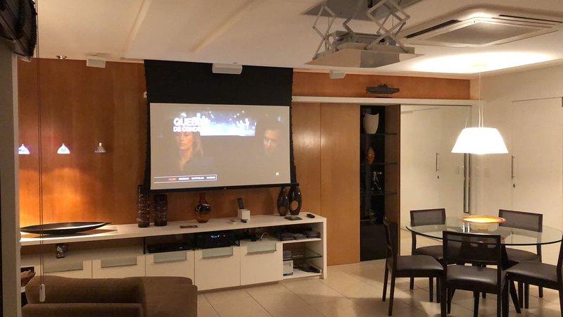 sala de estar con pantalla de cine, aire central empotrado en el techo