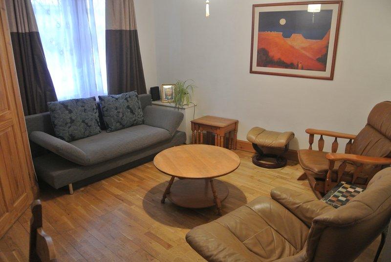Sala de estar amplia y luminosa, con sofá que se convierte en un sofá cama doble.