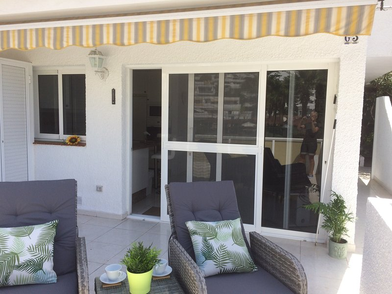 Sliding doors from living area onto terrace, fly screens separate.