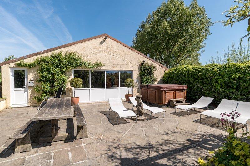 Extérieur du pool house - terrasse, coin table, chaises longues et bain à remous